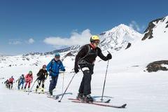 Narciarscy mountaineering mistrzostwa: grupowa narciarska alpinista wspinaczka na nartach na tło wulkanie obraz stock