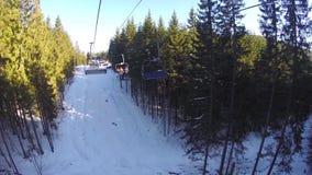 Narciarski dźwignięcie niesie ludzi up na górze Narciarki pochodzą od śnieżnych gór Ludzie są narciarstwem, wysokie świerczyny zdjęcie wideo