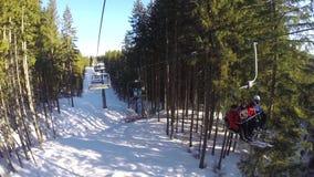 Narciarski dźwignięcie niesie ludzi up na górze Narciarki pochodzą od śnieżnych gór Ludzie są narciarstwem, wysokie świerczyny zbiory