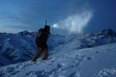 Narciarski krajoznawstwo mężczyzna popełnia wspinaczkę na nocy zimy górze Turysta z headlamp, plecak i snowboard za jego, popiera obraz stock