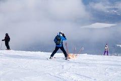Narciarski ratownik niesie pustego kołyska puszek góra pojęcie niebezpieczny łyżwiarstwo, freeride, ratuje zdradzonej narciarki fotografia stock