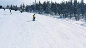 Narciarstwa i jazda na snowboardzie na narta ?ladzie blisko iglastego lasu w zimie w g?r? narciarskiego sk?onu i ludzi footage na obrazy stock