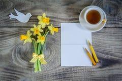 Narcisos amarelos com cartão e copo do chá no fundo de madeira ano novo feliz 2007 Foto de Stock Royalty Free