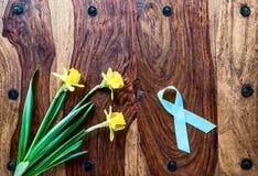 Narcisos amarelos e fita do câncer da próstata na tabela rústica Imagem de Stock