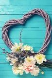 Narcisos amarillos, ramas del sauce y corazón decorativo en tur Imagenes de archivo