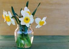 Narcisos en un florero de cristal en fondo de madera Imagen de archivo libre de regalías