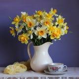 Narcisos en un jarro blanco y una taza retra en la tabla Foto de archivo libre de regalías