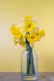 Narcisos en una botella en un fondo amarillo Fotos de archivo libres de regalías