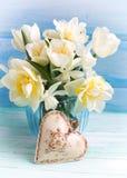 Narcisos y flores blancos brillantes de los tulipanes en florero y deco azules Imagen de archivo libre de regalías