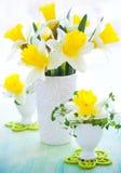 Narcissen in vaas en eierdopjes Stock Foto's