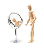 Narcissist wood mannekin over white. Narcissist wood mannekin looking at mirror over white Royalty Free Stock Photography
