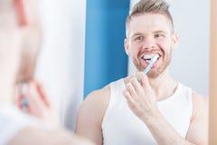 Narcissistisk man som borstar tänder Arkivfoto