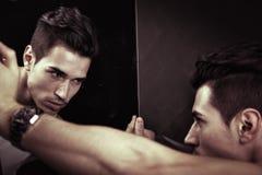 Narcissistisk ung man som beundrar hans reflexion Arkivfoto