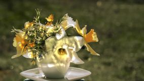 Narcissus bouguet. Narcissus and wild flowers bouquet and sun reflections in a coffee cup rotating against blurred grass background outdoors, close up side view stock video footage