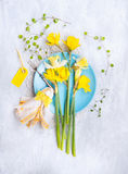 Narcissus bouquet on a blue plate with a yellow napkin , table decoration Royalty Free Stock Photo