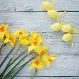 Narcissus Daffodils на деревянной белой квадратной предпосылке с декоративными пасхальными яйцами стоковое изображение rf