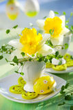 Narcissus in eggcups and easter eggs. Easter decoration: narcissus in eggcups and easter eggs on the table Royalty Free Stock Image