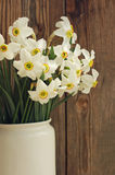 Narcissus flowers bouquet in the white vase in vintage style Stock Photo