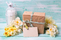 Narcissus flowers , empty tag for text , candle, box with presen Stock Photography