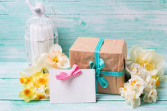 Narcissus flowers, empty tag for text , candle, box with present Royalty Free Stock Photos