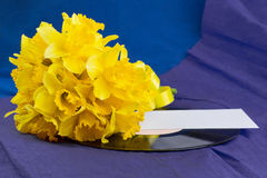 Narcissus flowers, envelope on background with vinyl record Stock Photo
