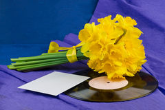 Narcissus flowers, envelope on background with vinyl record Royalty Free Stock Image