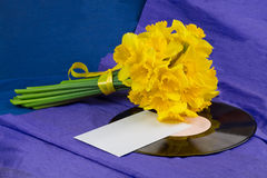 Narcissus flowers, envelope on background with vinyl record Stock Images