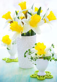 Narcissus in vase and eggcups. Easter decoration: narcissus in vase and eggcups Stock Photos