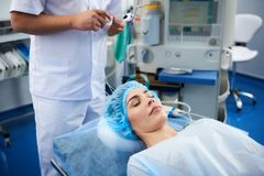 Young lady being under narcosis during the surgery in hospital stock photo