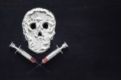 Narcotic powder in the form of a skull and syringes with injection. Copy space. The concept of addiction kills. royalty free stock photo