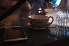 Nargile, Arabski wnętrze filiżanka herbaciani i cukrowi sześciany z różnymi smakami, handmade, smartphone na stole, wschodni obraz stock