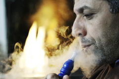 NARGUILÉ DE FUMAGE D'HOMME DU MOYEN-ORIENT Photo libre de droits