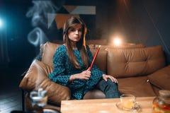 Narguilé de tabagisme de jeune femme au restaurant photo libre de droits