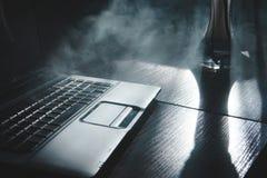 Narguil? de tabagisme tout en travaillant sur l'ordinateur portable ? la maison, th?me fonc?, fin, lignes de lumi?re du soleil image libre de droits
