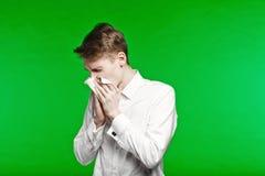 Nariz de estornudo y de funcionamiento del hombre joven Imagenes de archivo