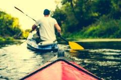 Nariz de la canoa que flota detrás de remero Fotografía de archivo