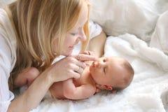Nariz recién nacida conmovedora de las hijas del bebé de la madre feliz Fotos de archivo