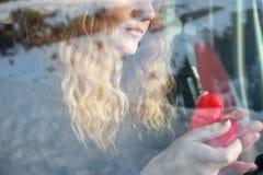 Nariz y boca de un retrato de una mujer atractiva joven con el pelo rizado rubio que se sienta cuidadosamente en el coche y que s imágenes de archivo libres de regalías