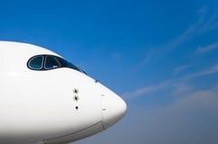 Nariz y carlinga de los aviones de los pilotos en un fondo del cielo claro azul Imagenes de archivo