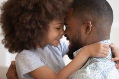 Narizes africanos pequenos bonitos do toque do abraço da filha com paizinho feliz foto de stock royalty free