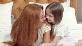 Narizes de fricção felizes da mãe e da filha, descansando em casa junto filme