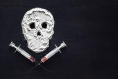 Narkotiskt pulver i form av en skalle och injektionssprutor med injektionen kopiera avstånd Begreppet av böjelsebyten royaltyfri foto