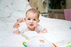 Narosły ślinotok w niemowlaku podczas ząbkowania Dziewczynka drooling w biel ubraniach kłama na białym łóżku, ono uśmiecha się, fotografia stock