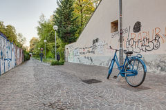 Narrow alley with bicycle. Narrow street in italian town - alleyway with bicycle and graffiti in the wall Royalty Free Stock Photo