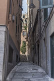 Narrow alley in Genoa city. An old tight alley, in the Italian specific antique architecture, in the historical center of Genoa city Royalty Free Stock Photo