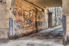 Narrow alley  in the old town. Narrow alley in the old town - corner of a decadent city street and grunge wall with graffiti Stock Photos