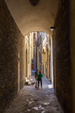 Narrow alley in the old town of Florence, Italy. Florence, Italy - July 06, 2016: narrow alley in the old town of Florence with undientified people. In medieval Stock Photos