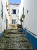 Narrow alley in the old town of Obidos, Portugal Royalty Free Stock Photo