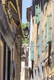 Narrow alley with pale ocher houses and turquoise shutters in a Royalty Free Stock Images