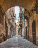 Narrow alley in Pisa, tuscany, Italy. Picturesque ancient italian alley with arch and ancient houses - typical narrow street in the old town of Pisa, Tuscany Stock Photo